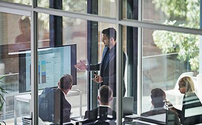 Ein Hueber Management Engineers Consultant erklärt einem Kunden ein Konzept am Tablet